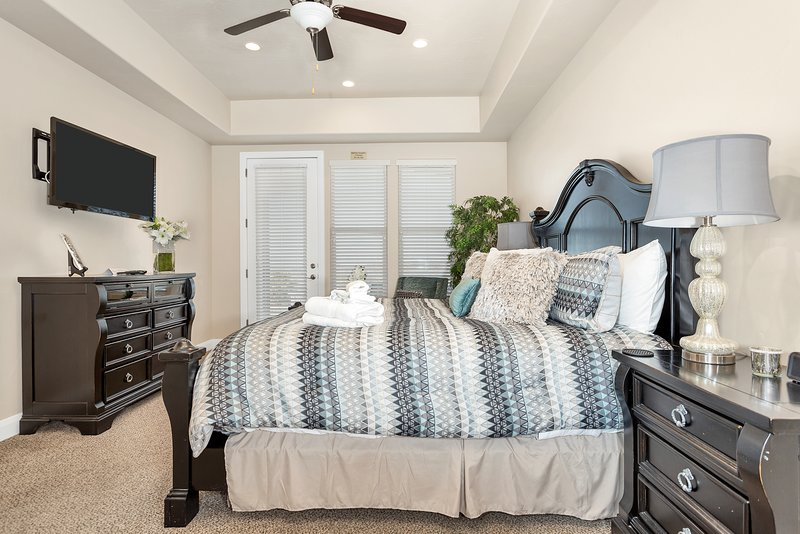 Master suite bedroom featuring a large flat screen tv