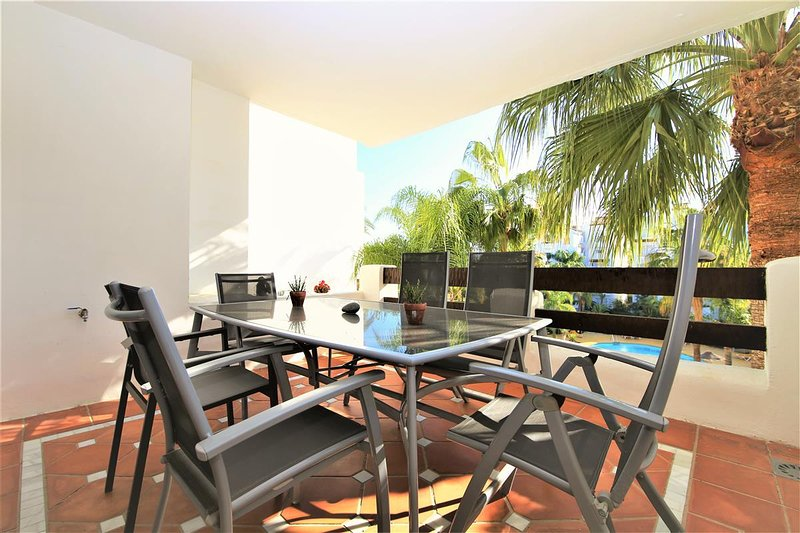 Lovely balcony overlooking the pool with dining table for up to six guests