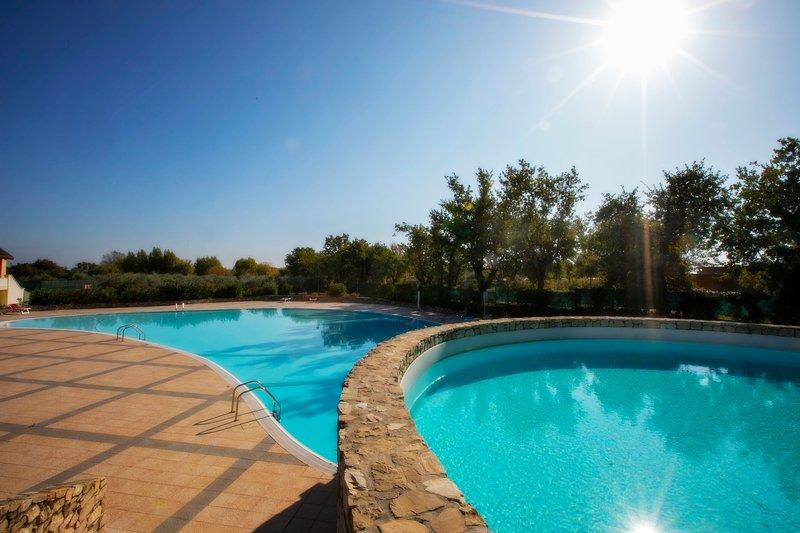 3 zwembaden in natuursteen omcirkelen de woning met uitzicht op het meer