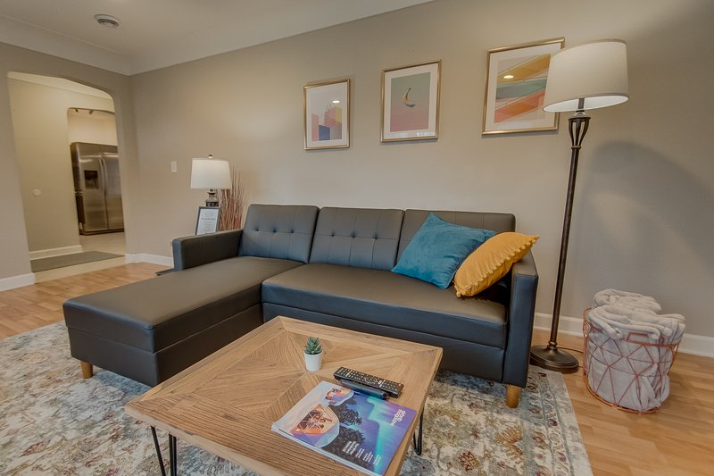 Sala de estar com TV grande, jogos e sofá secional
