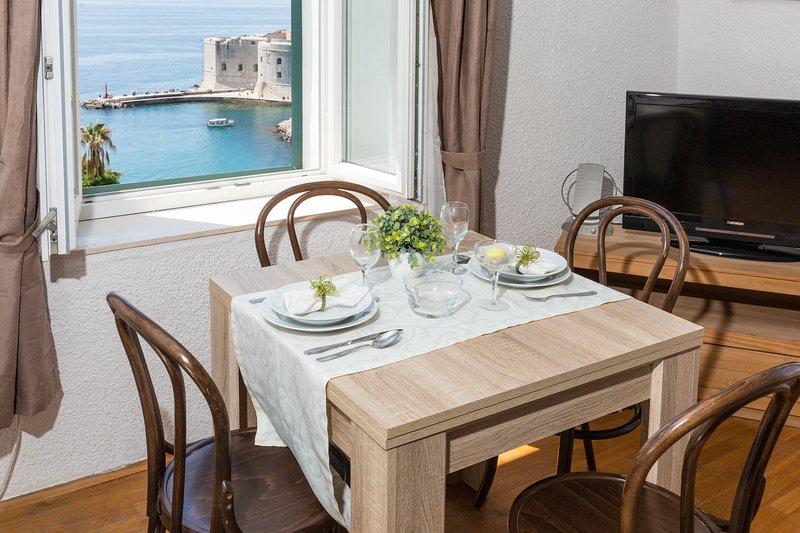 Sala de estar com mesa de jantar com vista para o mar