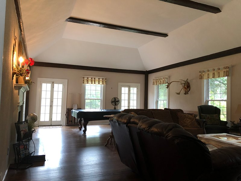Large great room with fireplace, reclining sofas, smart tv (Netflix available) and pool table.