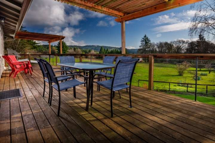 Expansive deck overlooking the yard, field, and acreage beyond.