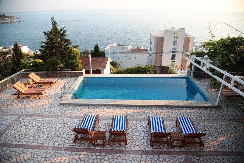 Vista sulla piscina con lettini e giardino con splendida vista sul mare