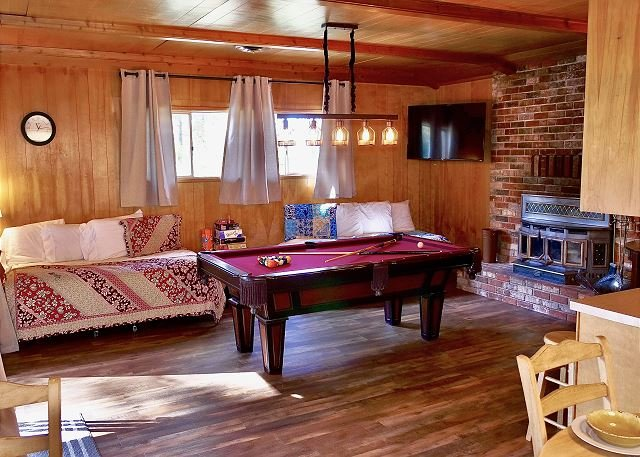 Game room with pool table, internet TV, fireplace and twin bed.