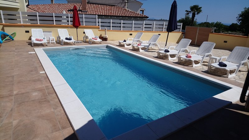 solarium area with 8 sunbeds, beach towels, umbrellas and tables