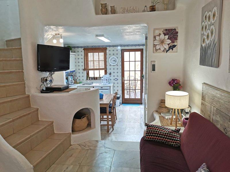 Split-level woonkamer met deur naar de patio vanuit de keuken en trap naar slaapkamer en badkamer
