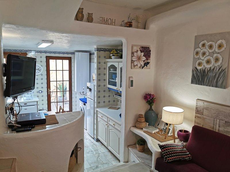 De split-level woonkamer heeft airco en heeft een deur van de keuken naar de patio