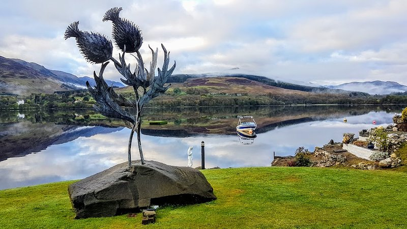 Thistle sculpture by blacksmith artist Kev Paxton in the garden on Loch Earn