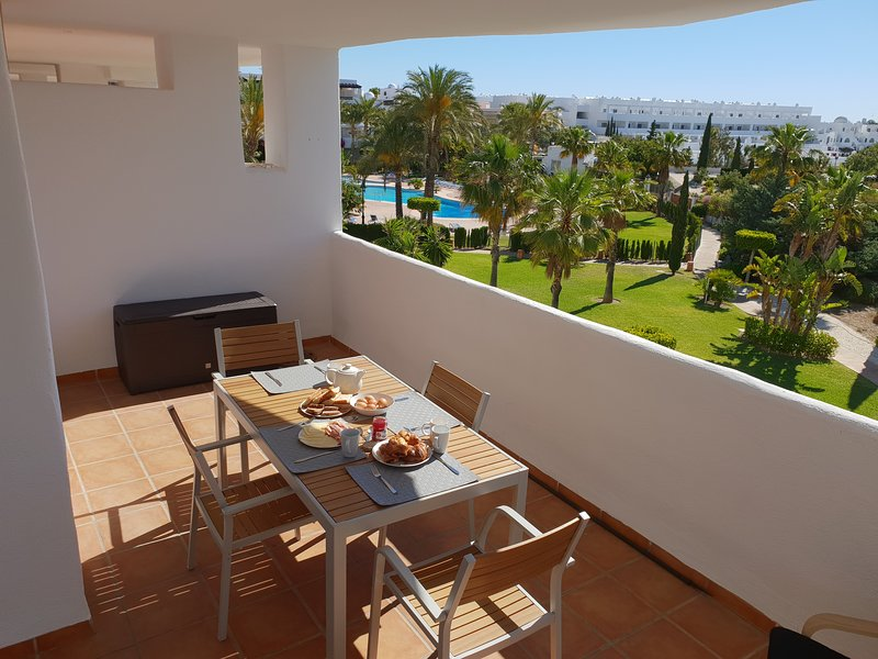 Beautiful outdoor balcony (1 of 2) with views over gardens to large pool. Partial sea views.