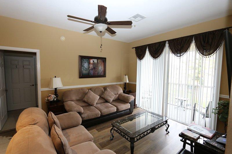 Salón con cómodos sofás, televisor inteligente montado en la pared, piso de madera nuevo y patio con puerta a balcón.