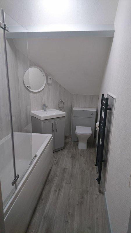 Gloednieuwe badkamer met bad en hoofddouche.