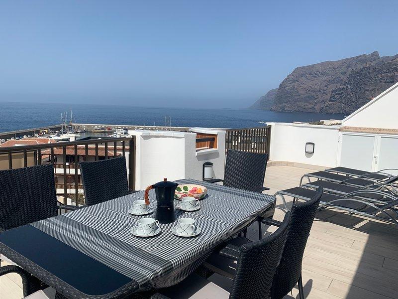 café en la amplia terraza, con los acantilados que se elevan por delante