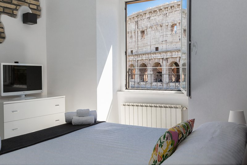 Bright bedroom with double bed and breathtaking view of the Colosseum.