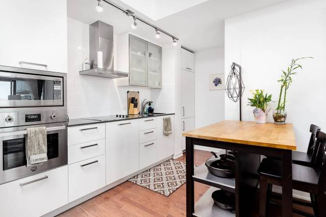 Modern kitchen with oven, electric cooktop, full-size refrigerator, microwave, toaster, coffee maker & more