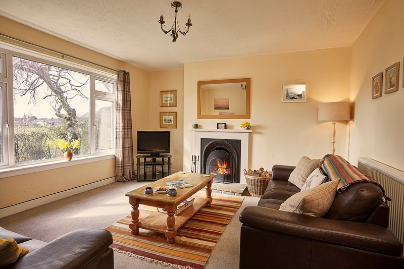 Light filled living room with huge west facing window looking out across fields towards the village
