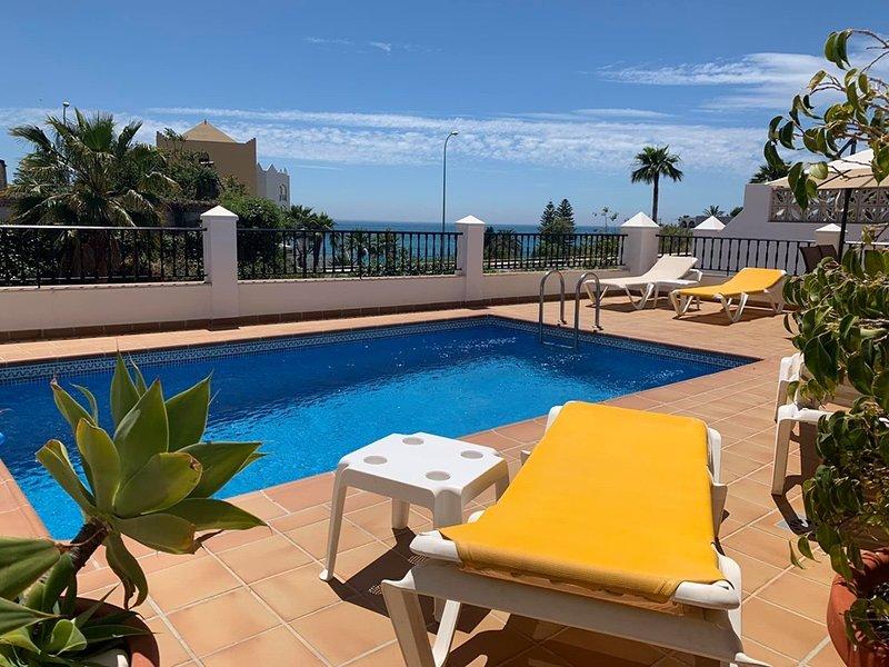 Patio principal con piscina privada y vistas al mar.