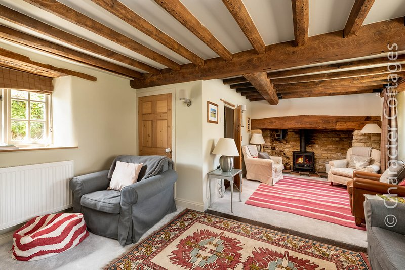 The inviting living room boasts a wonderful inglenook fireplace with a cosy wood burning stove