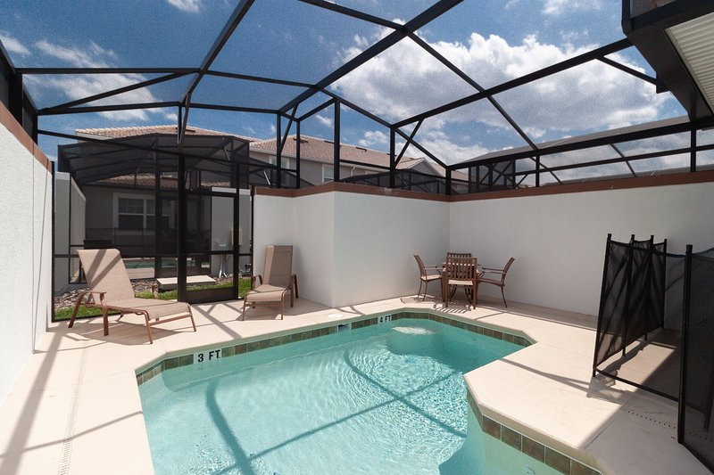 Enclosed back patio with a private pool and outdoor dining area.
