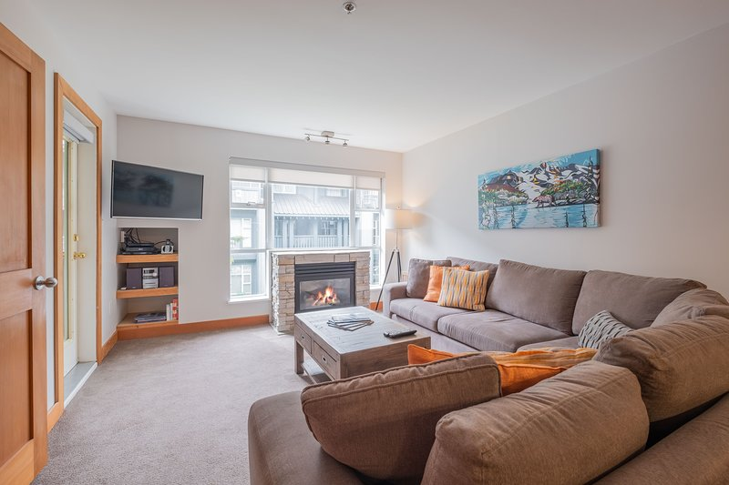 Spacious and inviting living area with flat screen smart TV, gas fireplace and pull out sofa bed.
