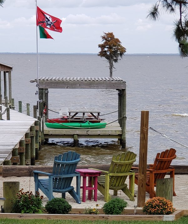 The picnic table over the water, kayaks, 3 chairs, hammock, and swing on the west side of the beach.
