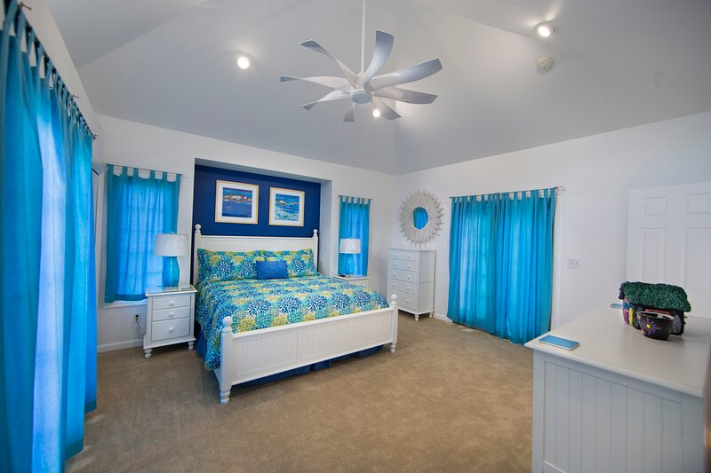 "Master Bedroom with King Bed, cathedral ceilings, large ceiling fan and private bathroom and 65"" TV."