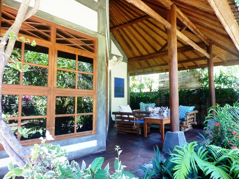 The front of the bungalow with the terrace. View to the garden, bamboo trees, fields until the sea.