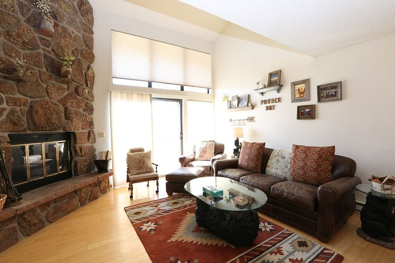 Living room with fireplace, vaulted ceilings and TV
