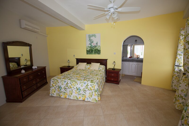 Bedroom one with queen size bed and air conditioning
