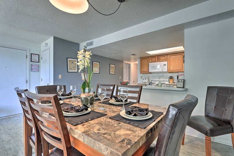 The condo features a fully equipped kitchen and dining table.