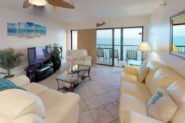 Large Beach Facing Living Room with comfortable seating and large flat screen TV.