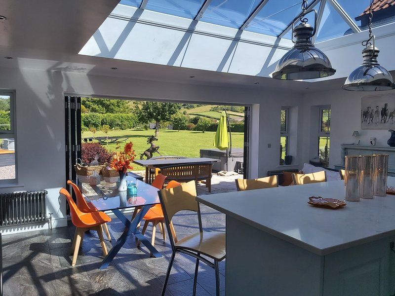 The large kitchen with casual dinning and a breakfast bar looks straight out on spacious garden.