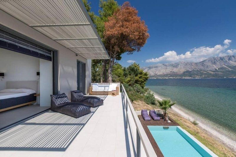 French doors open the full length of the bedrooms onto a balcony that has loungers and seating. Stunning views over the bay.