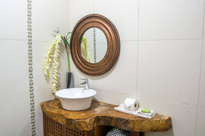 Bright bathroom with elegant wooden elements, a large floor-level shower and porcelain tiles.