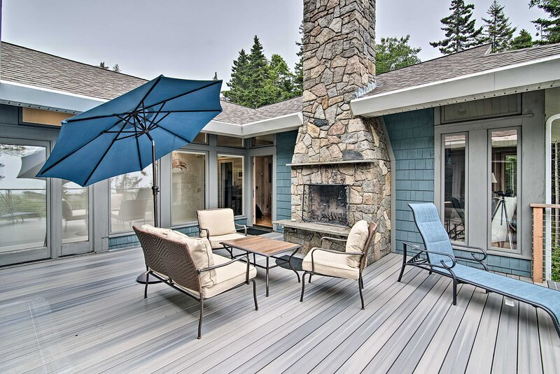 The home features a furnished deck with stunning views of the harbor.