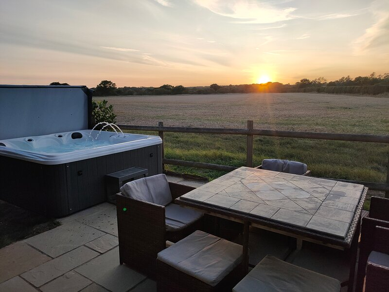 The Hay Barn private garden with hot tub and views over arable farmland.  Sun sets and tranquility.