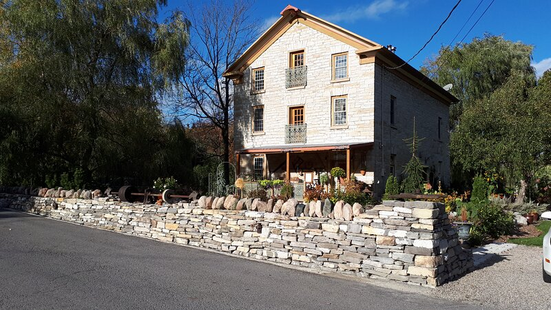 Front view of the mill 2020 with drystone wall and balconies.