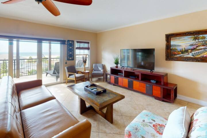 Spacious Living Room Space with Beach Views and Large Flat Screen TV.