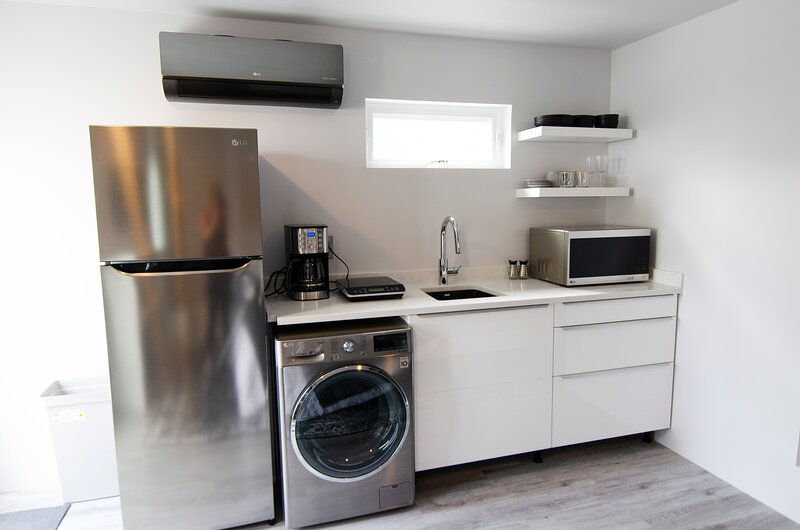 Kitchen with LG Refrigerator, W/D combo, Microwave, Induction Burner & Coffee Maker.