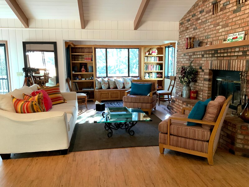 The cozy large living room with massive brick fireplace