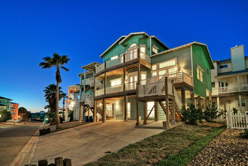 Three story house with decks across the front with partial beach views