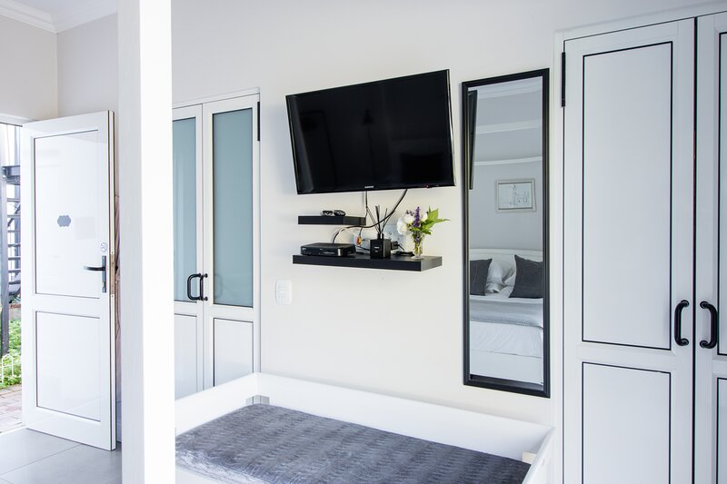 door to left of television leads to bathroom, door to the right leads to the kitchenette.