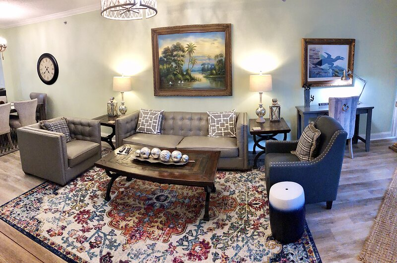 Spacious, updated living area with leather furniture, new flooring, rugs and lidghting.
