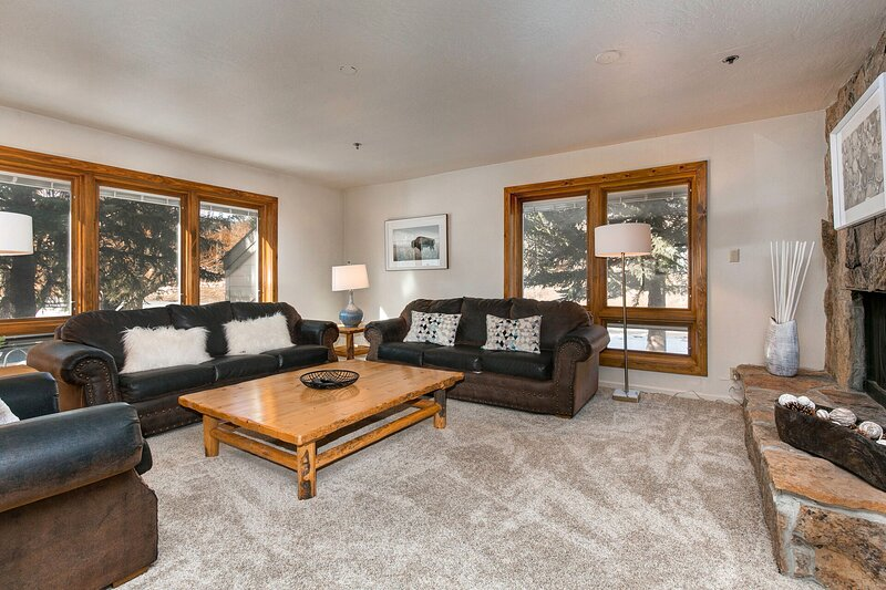 """Spacious Living Room with rustic leather furniture, gas fireplace, 65"""" LG smart tv, and large sleeper sofa"""