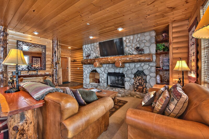 Living Room with Comfortable Mountain Furnishings, a Queen Sleeper Sofa, Stone Fireplace, Flat Screen TV and Mountain Views