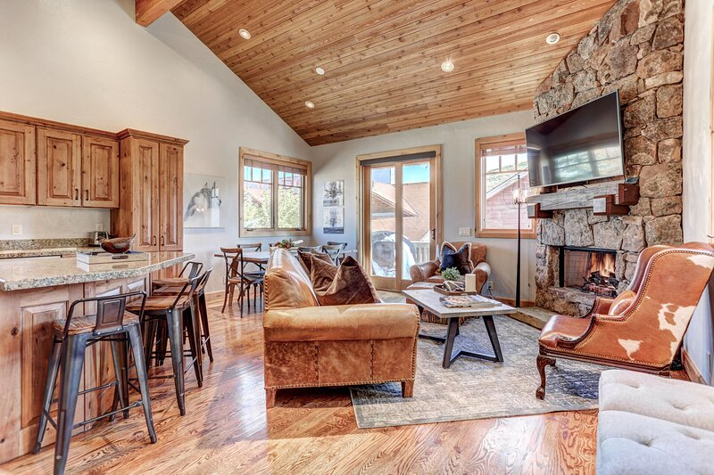 Living room with fireplace, 55' HD Smart TV, dining area and private deck