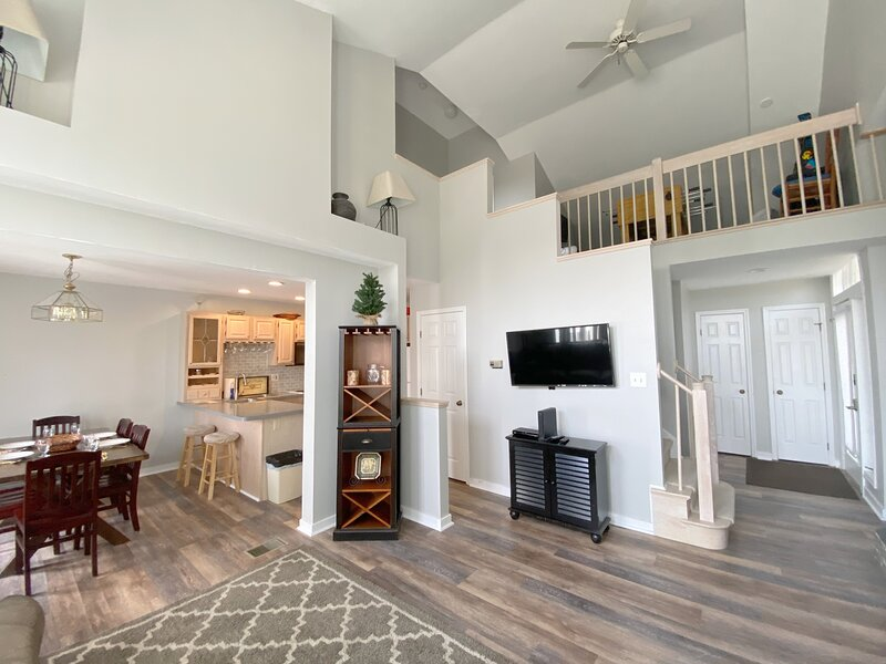 View from living area to loft, entrance, dining and kitchen areas