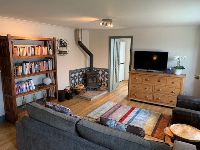 Cosy sitting room with wood burning stove and smart TV