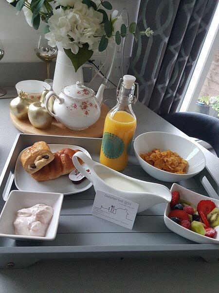Cereal breakfast with fresh fruit, yogurt, croissant and pain au chocolate and orange juice.