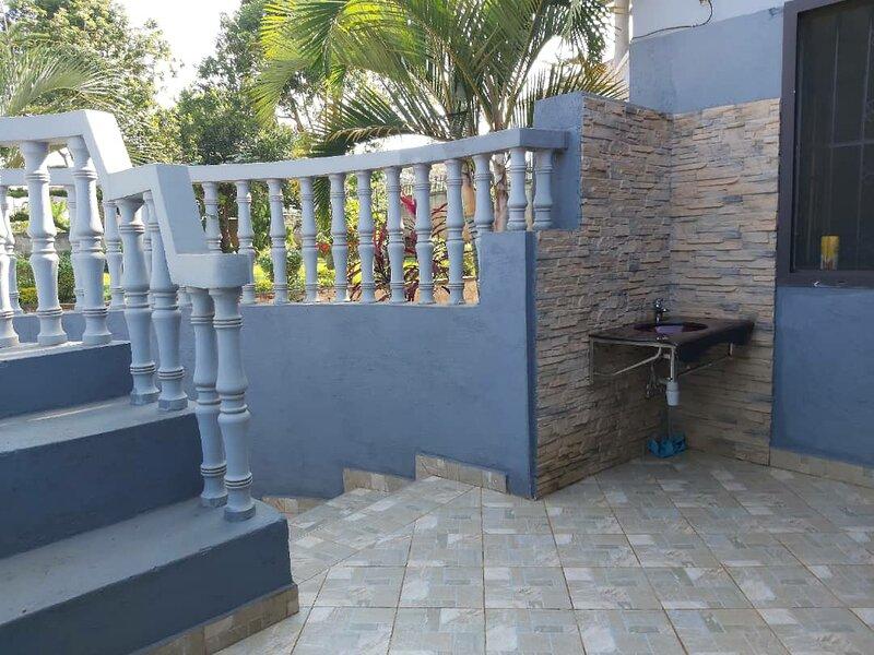 Double room guest wing with a living room, balcony and green lawn, aluguéis de temporada em Namugongo